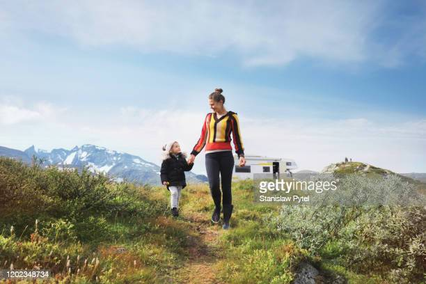 mother with daughter walking on wild road, campervan and mountains in background - encarando - fotografias e filmes do acervo