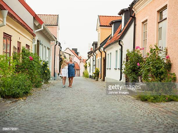 Mother with daughter walking through quiet street
