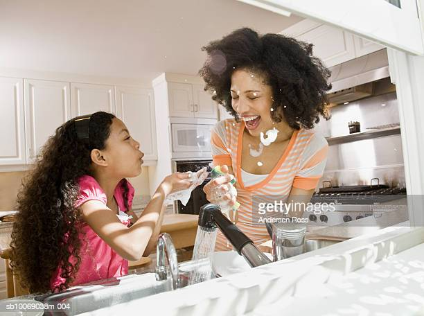 Mother with daughter (10-11) washing dishes in kitchen, playing with soap suds