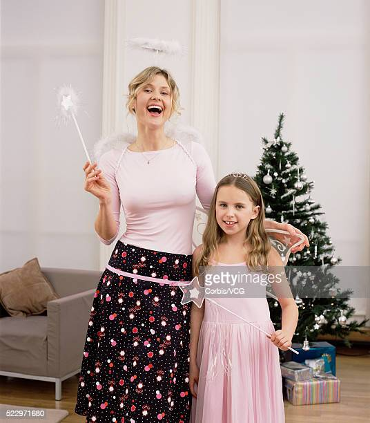 Mother with daughter wearing fairy costume at Christmas time