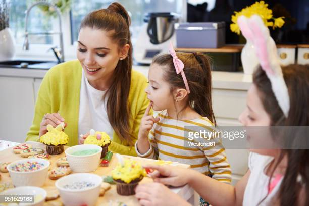 mother with daughters decorating easter cookies and muffins in kitchen - happy easter mom stock pictures, royalty-free photos & images