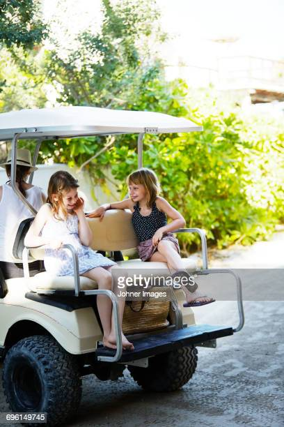 Mother with daughters in golf cart
