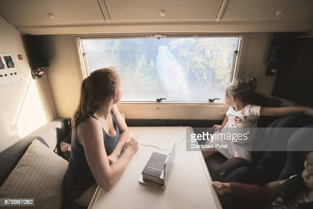 Mother with daughters looking through window of campervan on waterfall