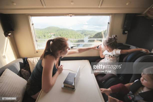 Mother with daughters looking through window of campervan on view
