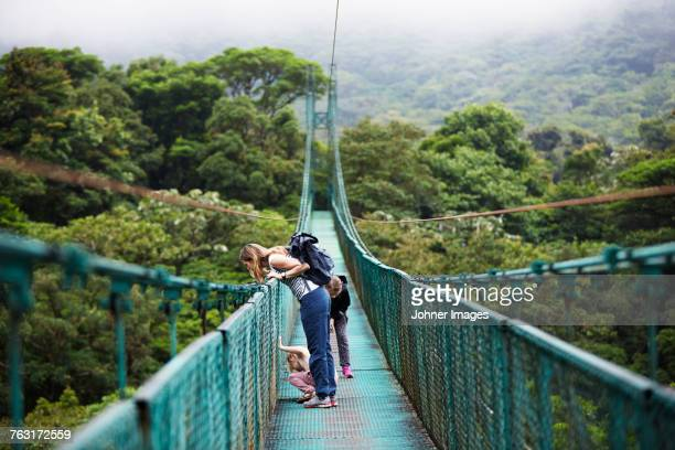 mother with daughters on hanging bridge - suspension bridge stock pictures, royalty-free photos & images