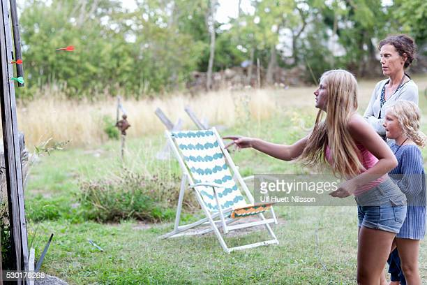 mother with daughters playing darts - darts girls stock photos and pictures