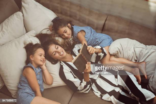 Mother with daughters reading books in bed
