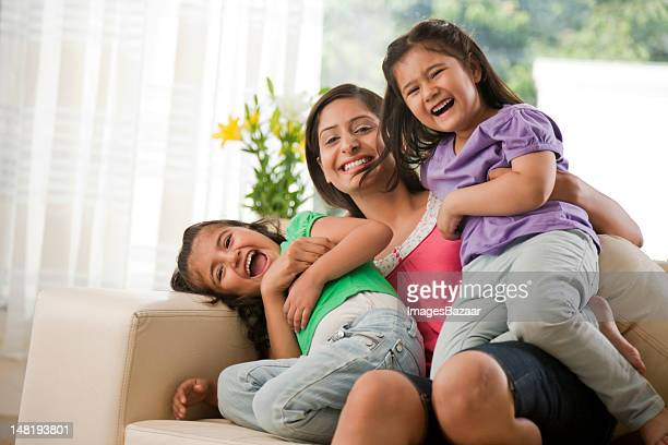 Mother with daughters (6-7) sitting on sofa