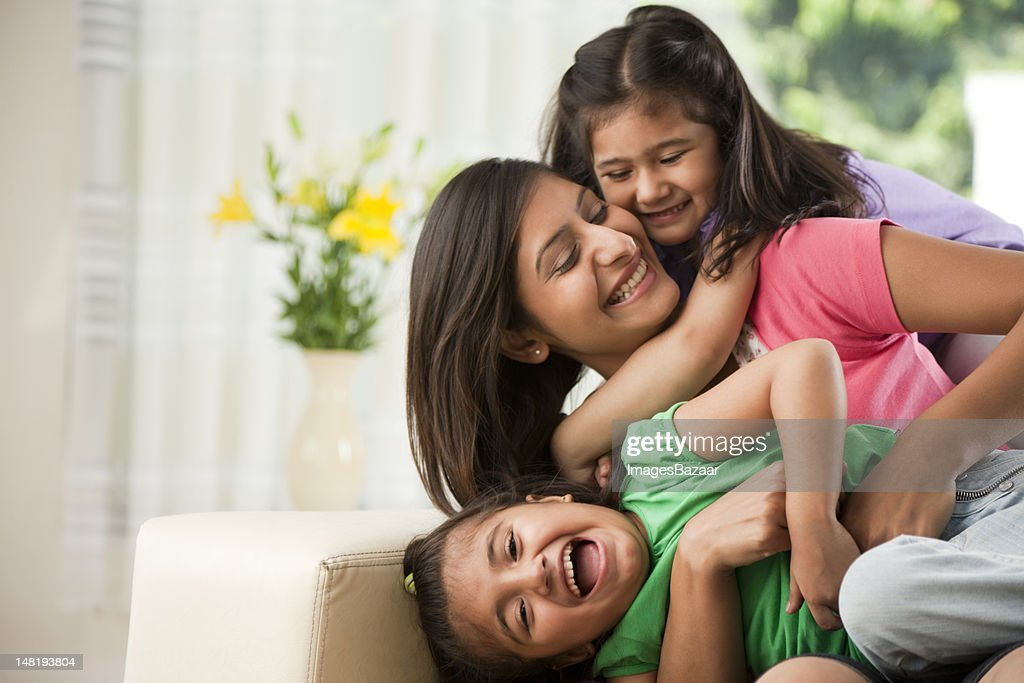Mother with daughters (6-7) sitting on sofa : Stock Photo