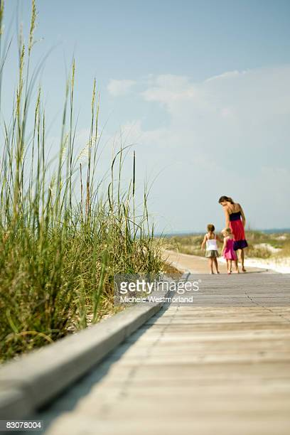 mother with daughters strolling on beach boardwalk - hilton head stock pictures, royalty-free photos & images