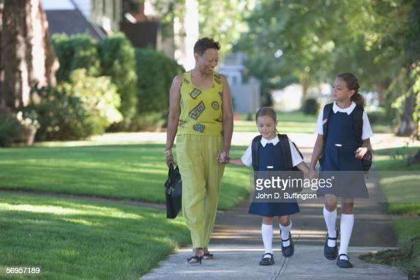 Mother with daughters walking down sidewalk