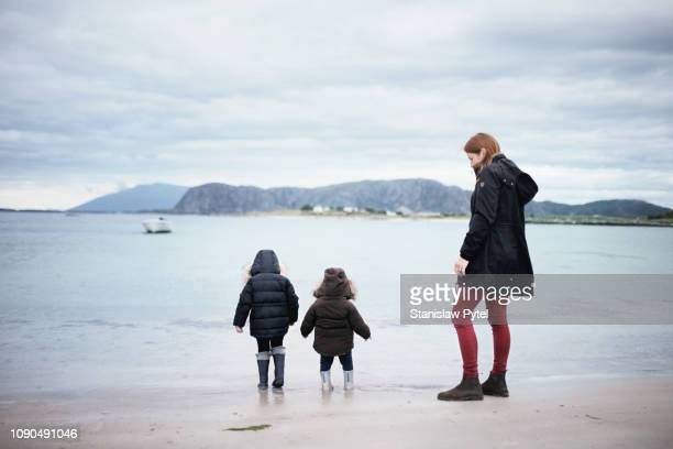 mother with daughters walking on cold norwegian beach - black boot stock pictures, royalty-free photos & images