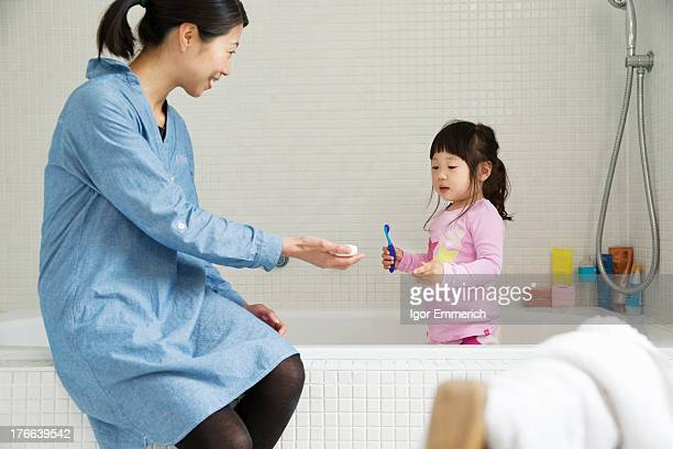 Mother with female toddler standing in bath with tooth brush