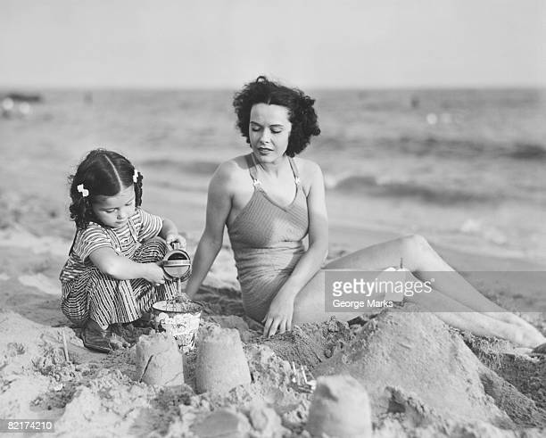 Mother with girl (2-3) playing in sand on beach, (B&W)