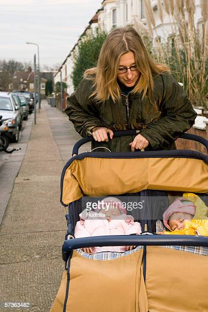 mother with girls in baby stroller on street, london, england - pink hat stock pictures, royalty-free photos & images