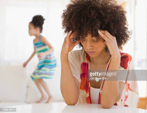 Mother with headache and daughter jumping on sofa