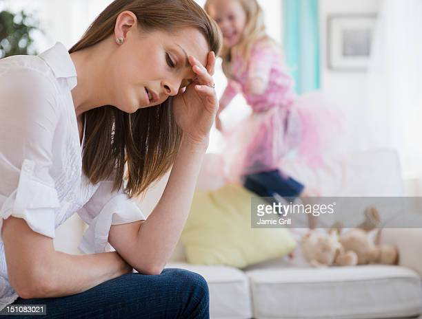 Mother with headache, daughter in background