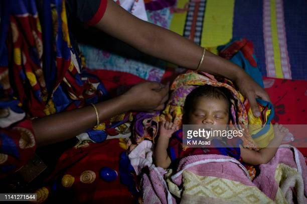 A mother with her 6 days old child take shelter in Khona Khatail government primary school in Dakop as Cyclone Fani approaches Bangladesh