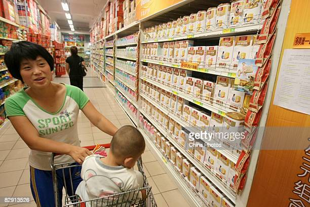 A mother with her baby buys milk powder products of foreign brands at a WalMart store on September 19 2008 in Changchun of Jilin Province China...