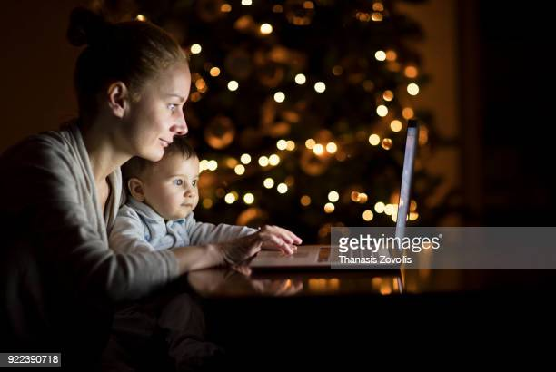 Mother with her baby looking a laptop in the dark