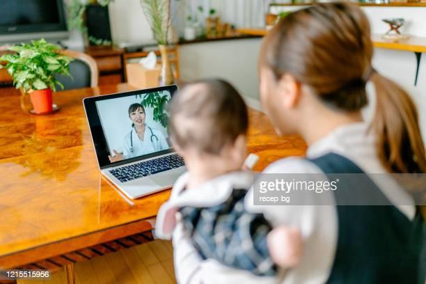mãe com seu vídeo bebê chamando médico de casa - exame médico procedimento médico - fotografias e filmes do acervo