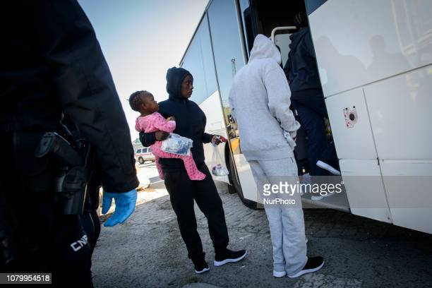 A mother with her child gets onto the bus to be transferred to a center on January 9 Malaga Southern Spain