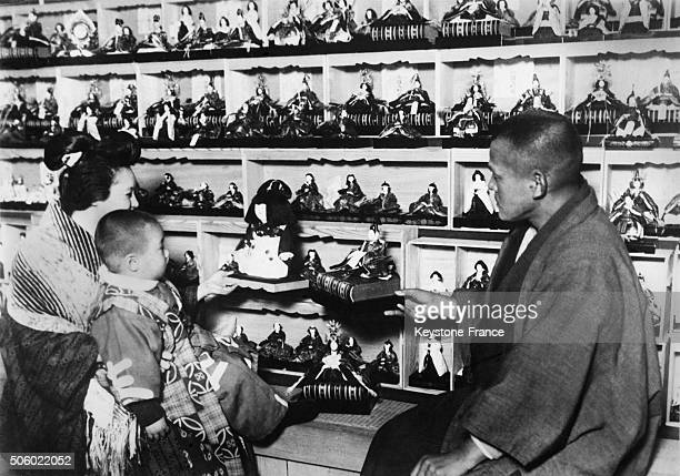 Mother with her child in a toy shop in Tokyo Japan looking at the dolls used for Hinamatsuri circa 1930