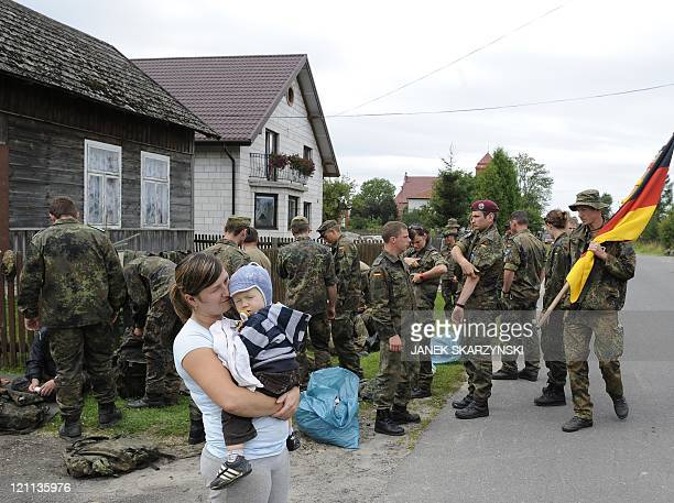 A mother with her child stand near a group of soldier pilgrims who will walk to the Marian shrine of Czestochowa on August 14 2011 in southern Poland...