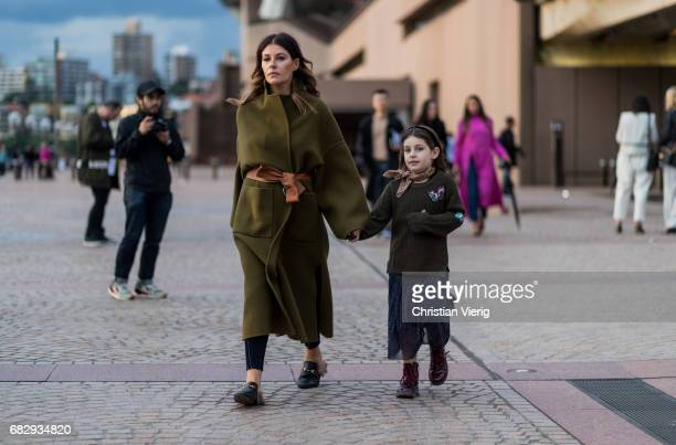 A mother with her child wearing a green wool coat with belt outside Dion Lee during MercedesBenz Fashion Week Resort 18 Collections at Sydney Opera...