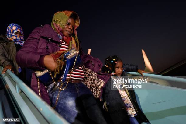 A mother with her children alights a chartered aircraft that brought home 150 migrants from Libya at the Murtala Mohammed International Airport in...