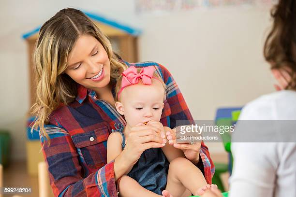 Mother with her cute toddler daughter practice sign language
