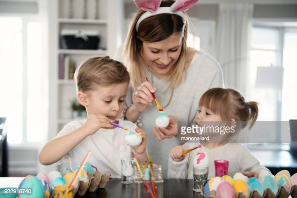mother with her daughter and son painting easter eggs. - happy easter mom stock pictures, royalty-free photos & images