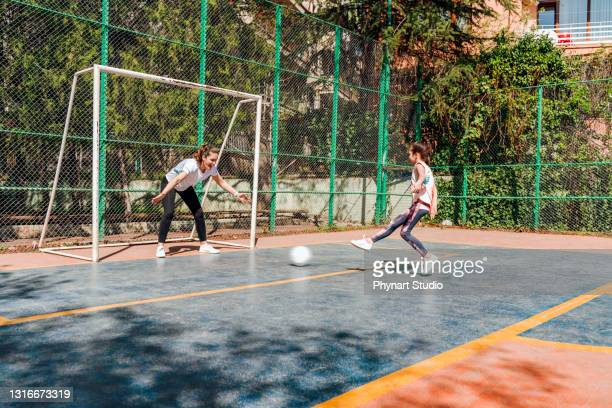 mother with her daughter playing saccer outdoors - shooting at goal stock pictures, royalty-free photos & images