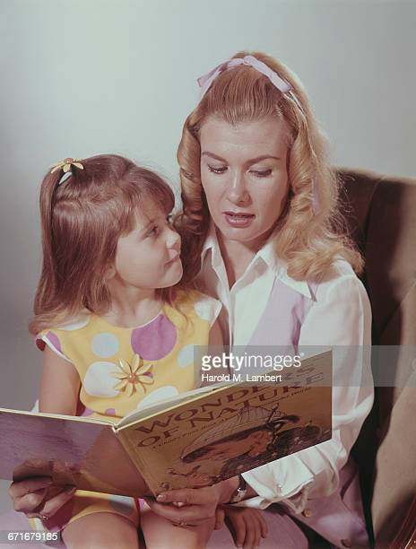mother with her daughter reading book in home  - daughter photos stock pictures, royalty-free photos & images