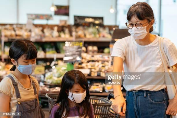 病気予防のための保護フェイスマスクを着用しながら、スーパーマーケットで買い物をする娘と一緒に母親 - コンセプト ニューノーマル ストックフォトと画像