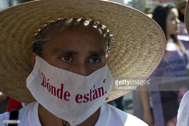A mother with her face partially covered with a surgical mask reading 'Where are they' participates in a protest during commemoration of the Mother's...