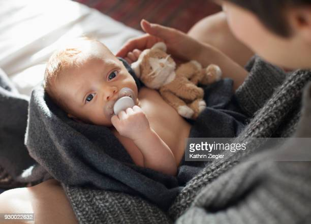 mother with her newborn baby wrapped in a blanket - pacifier stock pictures, royalty-free photos & images