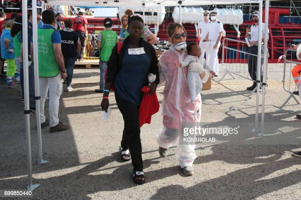 A mother with her son and a volunteer during a stages of disembarking from Vos Hestia of Save the Children with 507 SubSaharan immigrants aboard They...