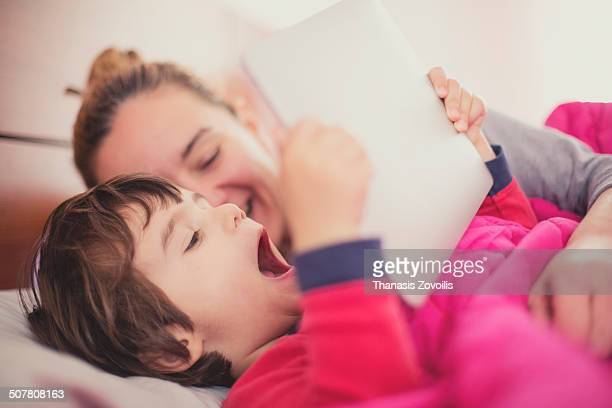 mother with her son using a tablet - yawning mother child stock photos and pictures