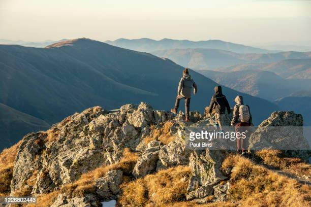mother with her sons descending from buteanu peak in fagaras mountains, romania - wandern stock-fotos und bilder