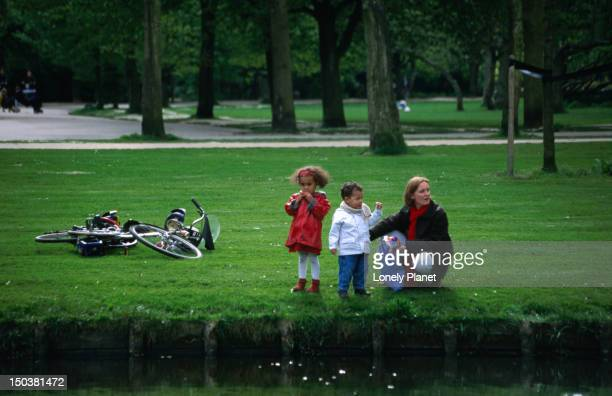 A mother with her two children at a pond in Vondelpark.