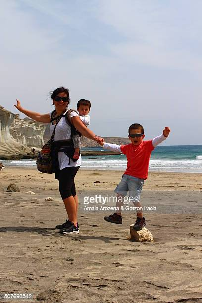 Mother with her two small children on the beach