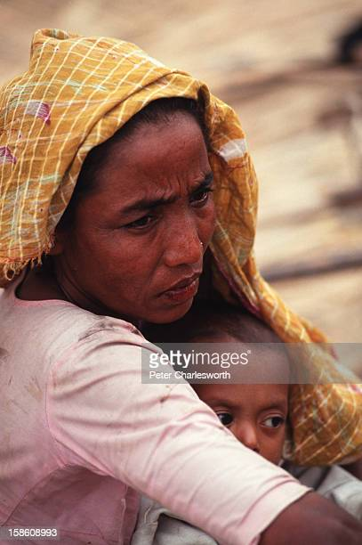A mother with her young child sit waiting for emergency relief after surviving one of the biggest cyclones to hit Bangladesh in recent decades...