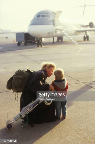 mother with her young son near a plane - image stock-fotos und bilder