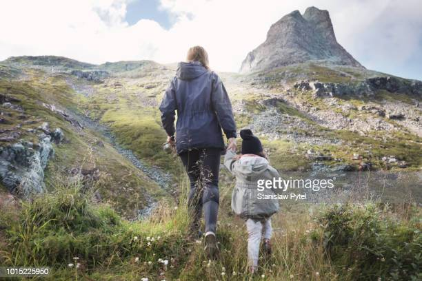Mother with kid in mountains,  admiring view