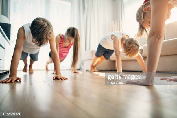 mother with kids exercising at home - push ups stock pictures, royalty-free photos & images