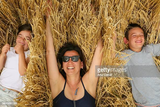 Mother with kids having fun on wheat field