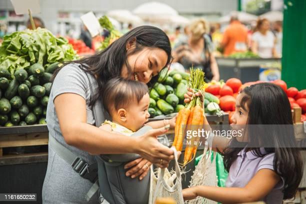 市場で買い物をする子供を持つ母 - ファーマーズマーケット ストックフォトと画像