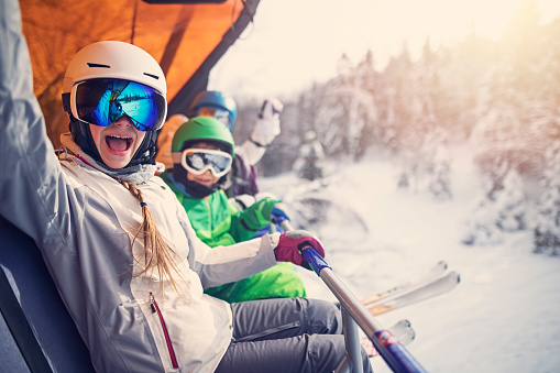 Mother with kids sitting on a ski lift 927410780