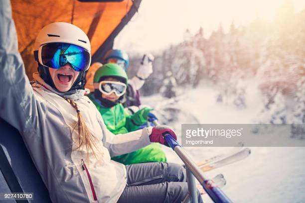 mother with kids sitting on a ski lift - winter sport stock pictures, royalty-free photos & images